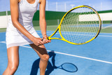 Midsection of tennis player woman ready playing game on blue hard court outdoor in position holding racket wearing white dress skirt. Female athlete sporty girl for summer sports activity course.