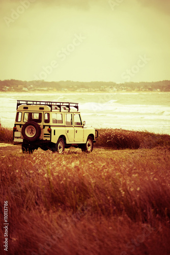 Summer adventure in retro car with beach landscape - 110113786