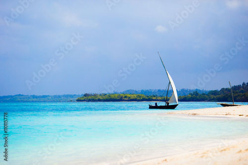 Deurstickers Zanzibar Old wooden dhow on white beach in the Indian Ocean