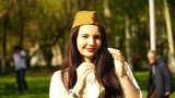 woman wears Soviet military hat outdoors.