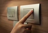 Fototapety finger is turning on a grey light switch.