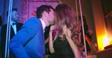 Beautiful young man and woman kissing at the party while their friends dancing behind them