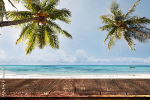 Old wood table with blurred sea and coconut tree background - Empty ready for your product display montage. Concept of beach in summer