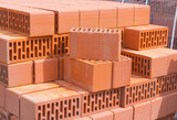 Fototapety Wall  ceramic perforated blocks of red bricks on a pallet