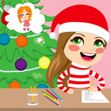 Cute little happy girl thinking and writing wishlist letter of Christmas presents