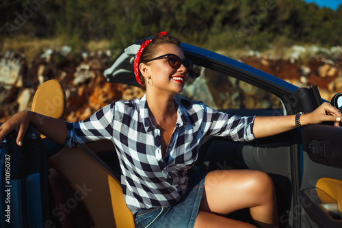 Foto op Canvas Snelle auto s Beautiful pin up woman sitting in cabriolet, enjoying trip on lu