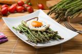 Asparagi verdi con uovo al tegamino su un piatto in ceramica bianco  ambientato