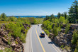 Cars driving on road in Acadia National Park, Maine, USA. The last car holds a canoe on its roof.