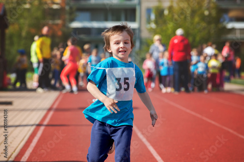 Young preschool children, running on track in a marathon competi