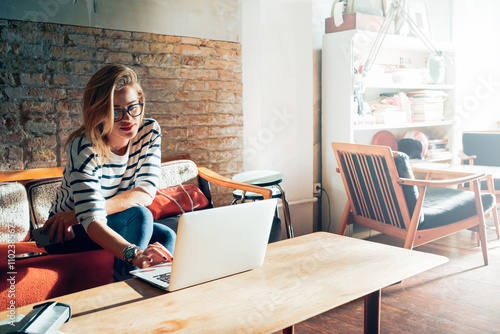 Beautiful young blonde female student using portable laptop computer while sitting in a vintage coffee shop.Young beautiful girl using a personal laptop computer to look up information on the internet