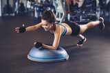 Asian sportswoman performing exercise on bosu ball