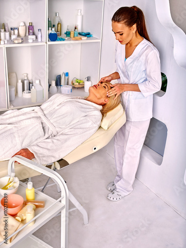 Fototapeta Woman middle-aged take face and neck massage in spa salon. Anti aging massage.
