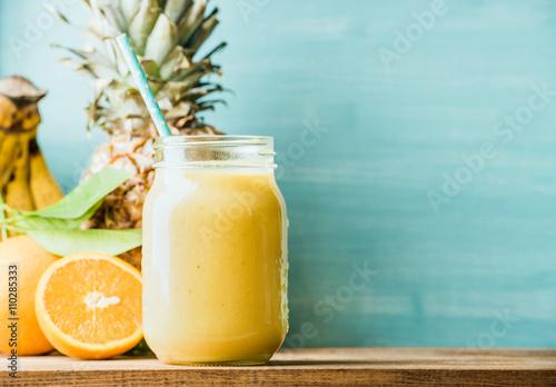 Świeżo mieszany żółty i pomarańczowy owocowy smoothie w szklanym słoju z słomą