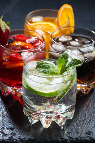 assortment of iced fruit drinks on a dark background, vertical