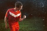 Fußballer feiert den Sieg im Regen
