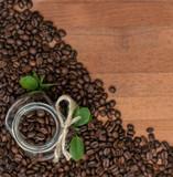 Кофейные зерна россыпью и в банке  на деревянном фоне