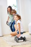 Mutter und Kinder haben Spaß mit Staubsauger