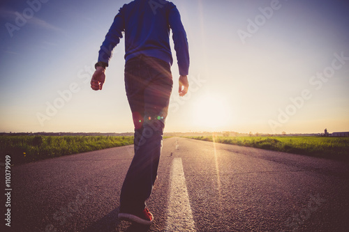 Poster Man walking on the line on a paved road
