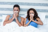 Young couple covering nose while sneezing on bed