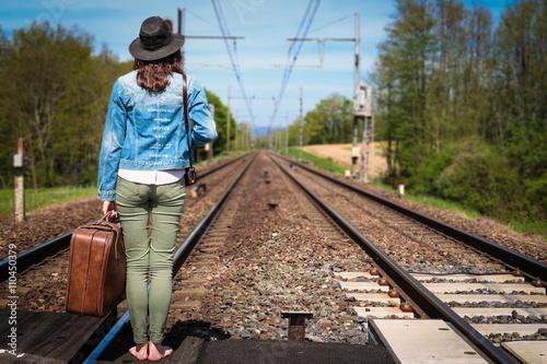 Papiers peints Voies ferrées Une jeune femme brune avec un chapeau attend un train au milieu des rails avec une valise à la main