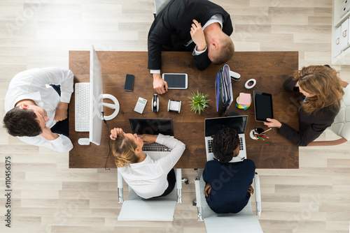 Tired Businesspeople Sleeping At Desk