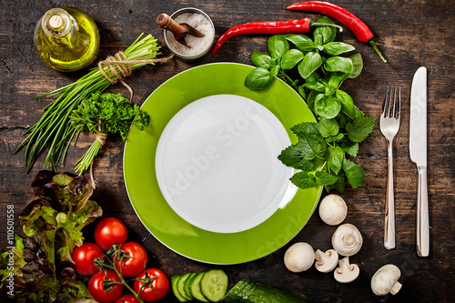 Plate Surrounded by Fresh Herbs and Vegetables