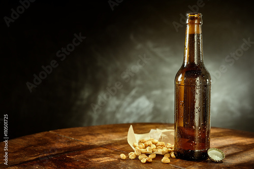 Bottle of Beer on Table with Peanuts and Cap