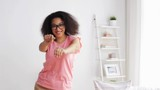 happy african american young woman dancing at home