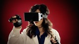 A doctor (a woman) wearing a virtual reality headset and wired gloves, examining a patient in the cyberspace.