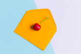 Fototapety  an isolated cherry on envelope, in a contemporarypastel color background