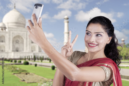 Poster Indian woman taking selfie at Taj Mahal