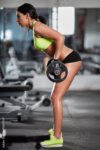 Fototapeta Woman doing barbell rows