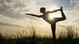 Silhouette female doing a one legged yoga pose at sunset