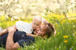 Baby Girl Hugging Father in Flower Meadow on Spring Day
