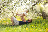 Happy Father lifting Baby Girl Playfully in Meadow