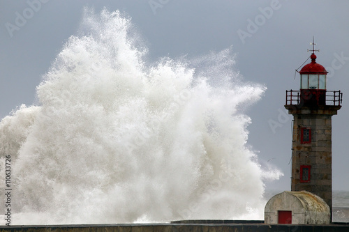 Stormy wave against lighthouse - 110633726