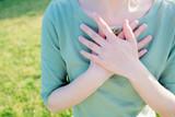 胸に手を当てる女性
