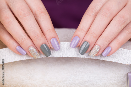 Manicure - Beauty treatment photo of nice manicured woman fingernails. Very nice feminine nail art with nice purple,silver and grayish nail polish.  © tamara83
