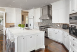 Kitchen in New Luxury Home with White Cabinets, Hardwood Floors, and Stainless Steel Appliances