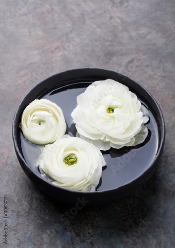 White floating ranunculus flowers. Spa wellness background © annapustynnikova