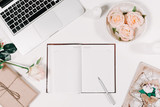 Fototapety Workspace with diary, pen, vintage white tray, pink rose, gift in parchment on white background. Top view, flat lay