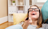 Young woman laughing while watching TV