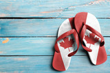 Thongs with flag of Canada, on blue wooden boards