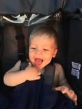 Happy caucasian baby boy in a stroller