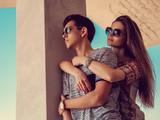 Attractive couple in sunglasses under blue sky.