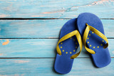 Thongs with flag of EU, on blue wooden boards