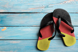 Thongs with flag of Germany, on blue wooden boards - 110710325