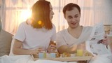 Young couple spending their morning in bed: woman drinking orange juice and eating croissant while man reading hilarious article in newspaper, showing it to his wife and they laughing together
