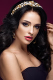 Beautiful brunette model: curls, classic makeup, gold jewelry and red lips. The beauty face.