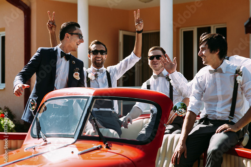 Boys in the sunglasses in the old red car плакат